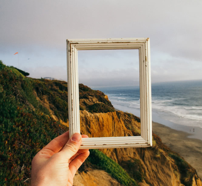 Hand holding up an empty picture frame in front of beachfront cliffs